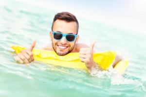 Junger Mann schwimmt auf gelber Luftmatratze