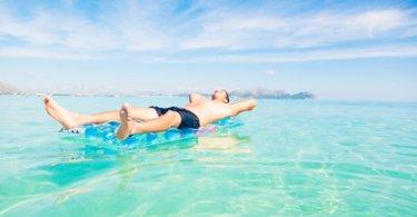 Junger Mann entspannt auf blauer Luftmatratze bei schönem Wetter auf dem Wasser
