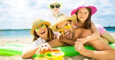 Junge Familie, die sich im Urlaub am Strand auf grüner Luftmatratze freut
